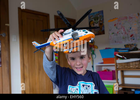 Boy aged four years playing with Lego building blocks helicopter, in bedroom - Stock Photo