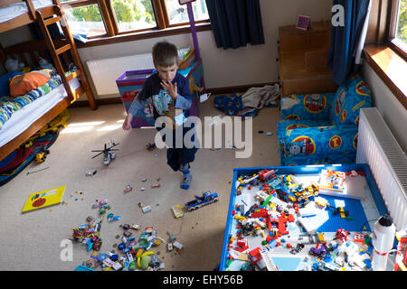 Boy aged four years playing with Lego building blocks in bedroom - Stock Photo