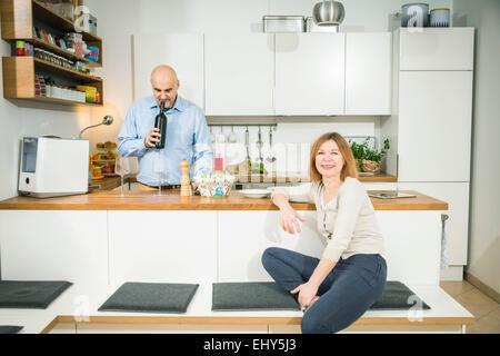 Senior man smelling wine cork in kitchen - Stock Photo