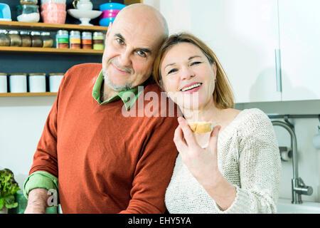 Senior couple in kitchen smiling happily - Stock Photo