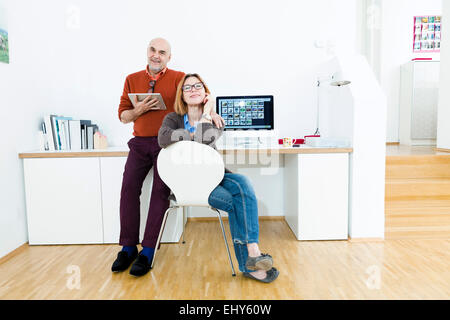 Senior couple using computer at home - Stock Photo