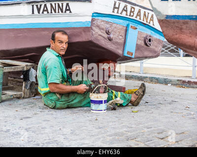 A Cuban man sits on the ground as he repairs his boat in Havana. - Stock Photo