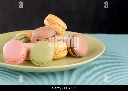 Assortment of gentle colorful macaroons on green ceramic plate on blue placemat background. - Stock Photo