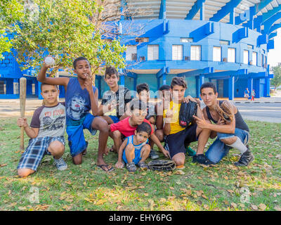 A group of young Cuban boys, who were playing a pick up game of baseball,  pose with their bat, ball and gloves - Stock Photo
