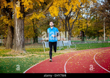 Male runner jogging on running track - Stock Photo
