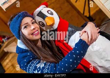 Young woman posing with penguin figurine - Stock Photo