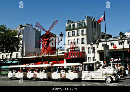 Tourist mini train passing through the Moulin Rouge theater, Pigalle, Paris, France. Red Windmill. City tour, sightseeing. Iconic landmark. Copy space