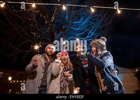 Group of friends with sparklers having fun - Stock Photo
