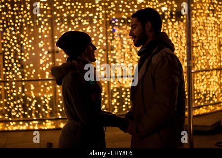 Young couple falling in love at Christmas Market - Stock Photo