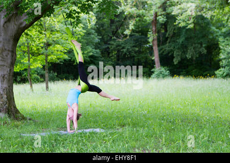 Young woman does stretching exercises with rubber band, Munich, Bavaria, Germany - Stock Photo
