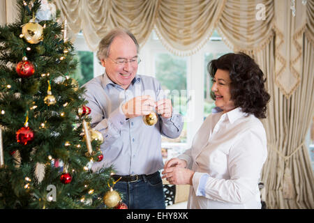 Senior couple decorating Christmas tree together - Stock Photo