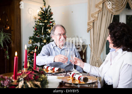 Senior couple drinking champagne at Christmas - Stock Photo