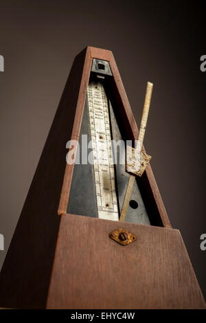 Color shot of a vintage metronome, on a black background. - Stock Photo