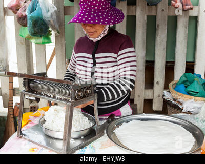 A busy fish trade in the early morning near Hoi An, Vietnam. A woman cutting rice noodles for breakfast. - Stock Photo