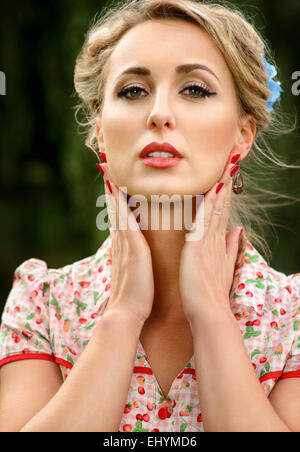 Portrait of a mid adult woman holding her hands to her face - Stock Photo