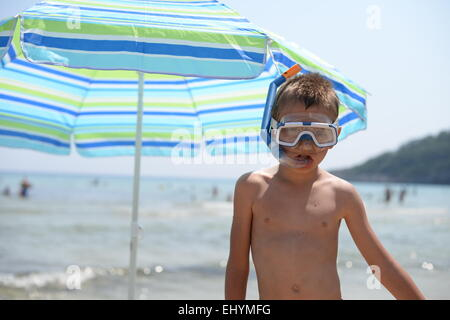 Boy wearing snorkel and mask standing on the beach, Thassos, Greece - Stock Photo