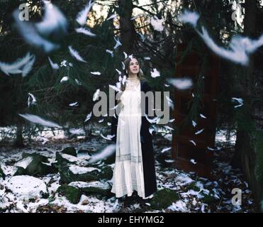 Young woman standing in forest with feathers falling all around - Stock Photo