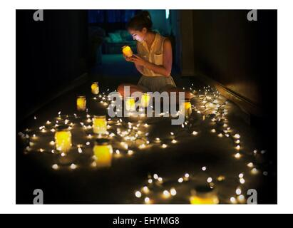 Young woman sitting on floor surrounded by lights and jars - Stock Photo