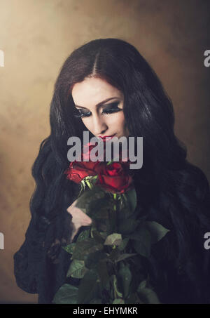 Portrait of a woman in black holding bunch of red roses