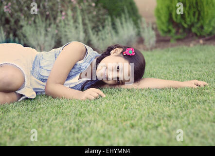 Portrait of a smiling girl lying on grass - Stock Photo