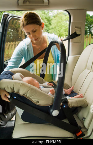 Mother strapping baby boy in car seat - Stock Photo
