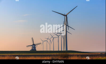 Rows of wind turbines and an old traditional windmill, Eemshaven, Groningen, Netherlands - Stock Photo