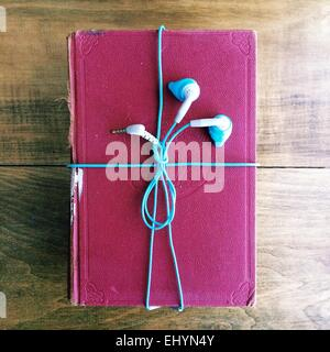 Headphones wrapped around an old book - Stock Photo