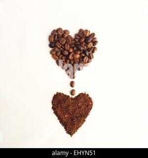 Coffee beans in a heart shape, dripping into another heart shape of ground coffee - Stock Photo