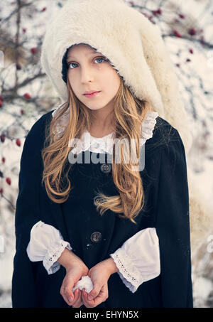 Sad looking girl holding snow in the shape of a heart - Stock Photo
