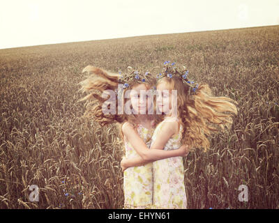 Girl standing in a wheat field hugging her alter ego - Stock Photo