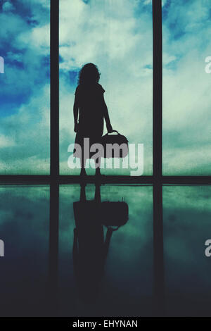 Silhouette of a girl standing at an airport window - Stock Photo