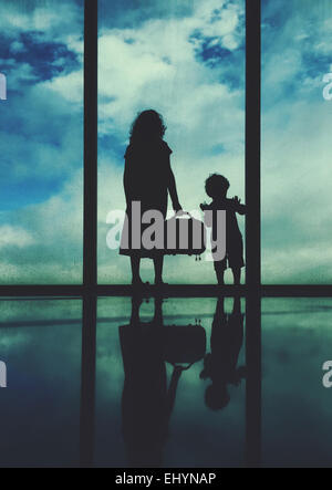Silhouette of a woman and boy standing at an airport window - Stock Photo