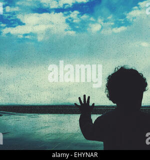 Silhouette of a boy looking out of an airport window - Stock Photo