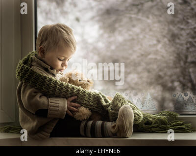 Boy sitting on a window sill with a teddy bear - Stock Photo