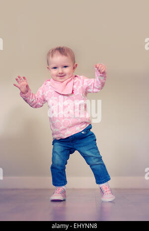 Baby girl taking her first steps - Stock Photo
