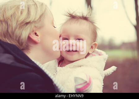 Mother kissing baby girl - Stock Photo