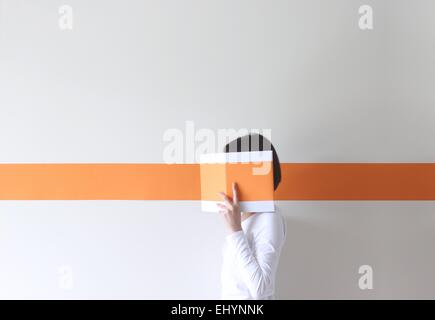 Side view of a mature woman hiding her face behind a book - Stock Photo