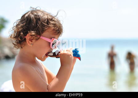 little girl eating ice cream on the beach of sea - Stock Photo