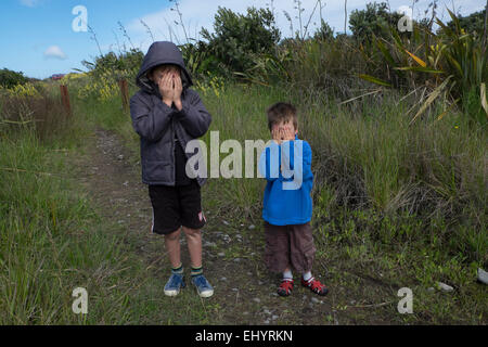 Children playing hide and seek in field - Stock Photo