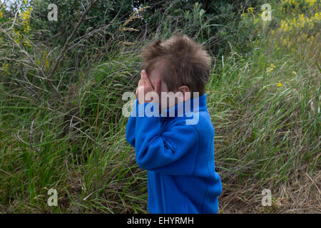 Child playing hide and seek in field, 4 year old boy - Stock Photo