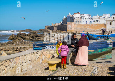 Family with fishing boats in front of the ramparts of the Old City of Essaouira, Morocco, North Africa - Stock Photo