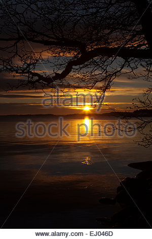 Rising sun on a winter morning in the archipelago of Turku Finland - Stock Photo