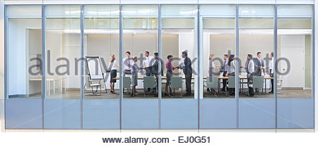 View through window, of people shaking hands in business meeting - Stock Photo
