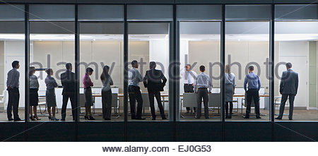 View through window, of people standing in business meeting - Stock Photo