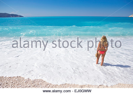 woman, looking out to sea, standing in sea on sunny beach - Stock Photo