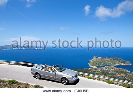 Senior couple driving convertible car along coastal road - Stock Photo