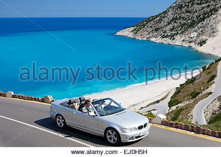 Family driving convertible car along winding coastal road - Stock Photo