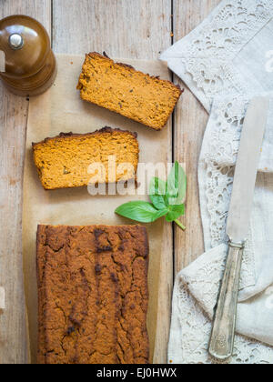 Vertical photo of a loaf of homemade vegetarian chickpea pate on a rustic wooden table, two pieces cut off. View - Stock Photo