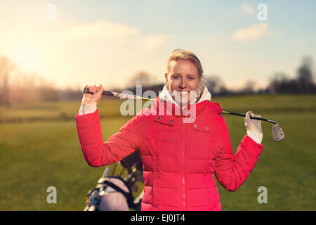Close up Smiling Young Female Golfer in Red Jacket Holding a Golf Club Over her Shoulder While Looking at the Camera.