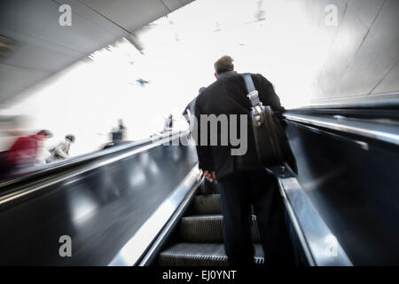 People on moving escalator, London tube - Stock Photo